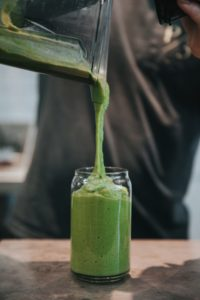 green smoothie being poured into a glass