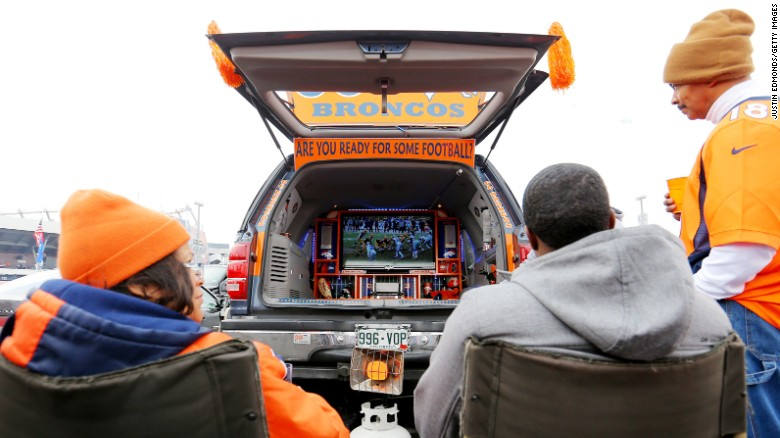 Football fans pregame with a TV and generator setup for tailgating