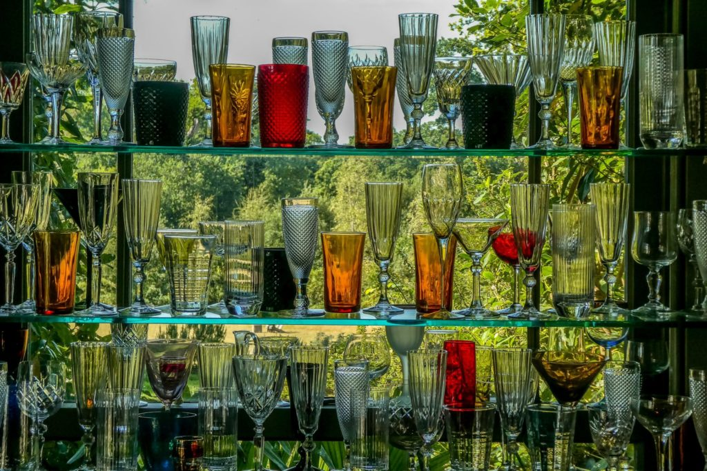 A wonderfully colourful collection of drink glasses, behind the bar.  Lit from the outside light.